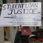 A protest sign calling for action regarding student loans.
