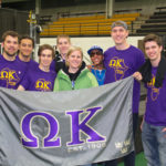 Members of Omega Kappa gathered with their brothers and flag at their first ever Africa Jam in 2014.