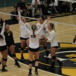 The Gustavus Women's Volleyball team celebrates on the court.