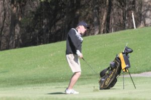 Junior Thomas Carlson aims for the green at the Gustie Invitational.