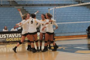 Members of the Gustavus volleyball team celebrate after earning a point.
