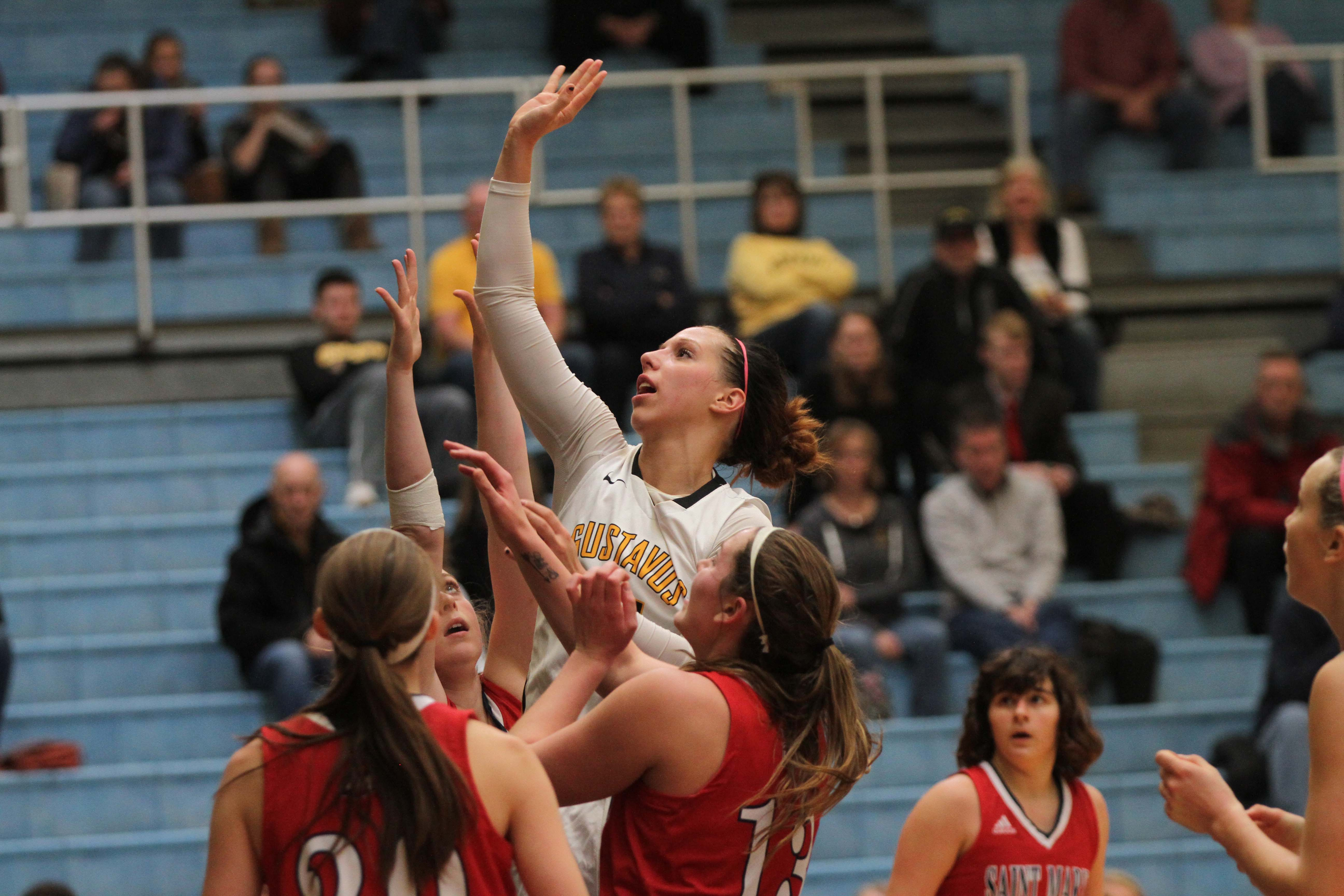 Sophomore Paige Richert attempts to tip the ball into the basket under pressure from three St. Mary's opponents.