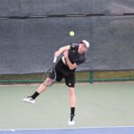 Senior Chase Johnson serves a ball during a match. The team got its second consecutive consolation title this past weekend at the ITA Indoor Championships.