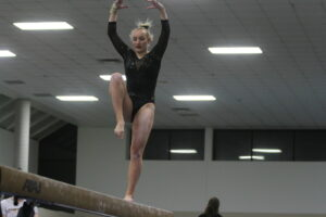 Senior Sam Ardy performs on beam during Senior Night March 1.