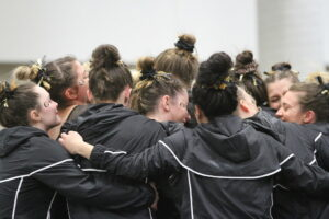 Members of the gymnastics team embrace the seniors at their final home meet.