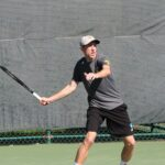 Senior Chase Johnson returns a ball during a match earlier this season. After sweeping conference opponents, St. Olaf and Hamline, the Gusties have improved their record to 8-2.