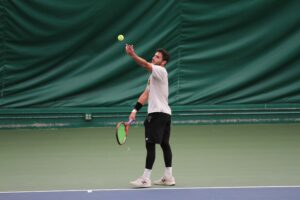 Junior Yassine Derbani serves the ball to his opponent during a match.