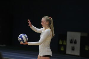 Junior Hailey Embacher prepares to serve the ball for the Gusties.