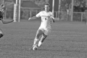 Senior Abby Mullenbach controls the ball in the midfield for the Gusties.