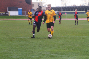 First-year Raphael Cattelin holds off a defender and dribbles towards goal.