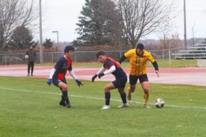 Junior Matthew Gibbons dribbles past a pair of Macalester defenders.