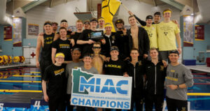 Members of the Men's Swimming team celebrate winning their second consecutive title.