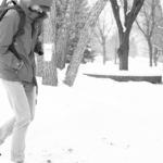 A student walking in front of the Jackson Campus Center during a heavy snowfall.