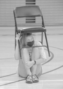 A hypnotized Gustie takes shelter under a folding chair.
