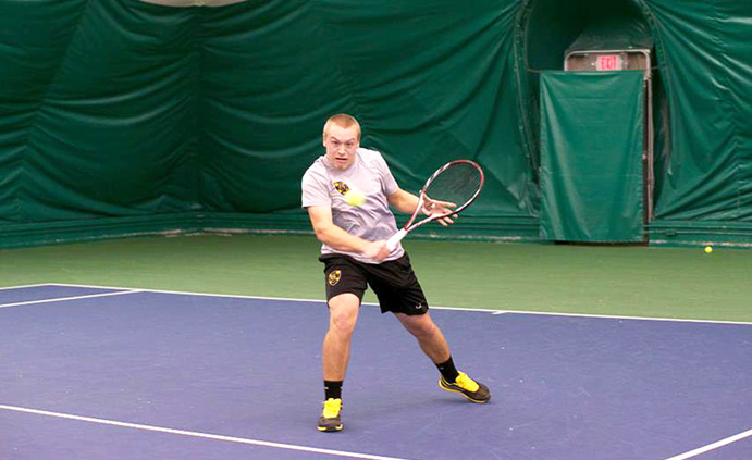 Sophomore Sam Hjelm works on perfecting his volley technique. The men's tennis team works hard in practice to ensure success in meets. <em>Submitted</em>