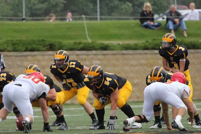 Quarterback Mitch Hendricks (#3) and the offense group prepare for the next play in their September game against Simpson College. The team is excited to take on conference rival St. Olaf in Saturday's Homecoming game. Gustavus Sports Information