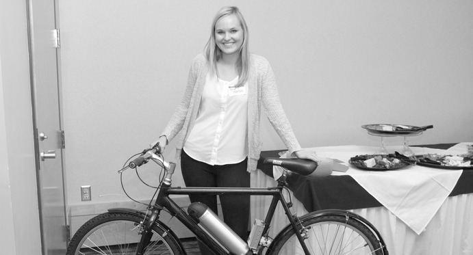Senior Erin Tollefson displays Power Assist Ride Share Bike. Gustavus Marketing and Communications