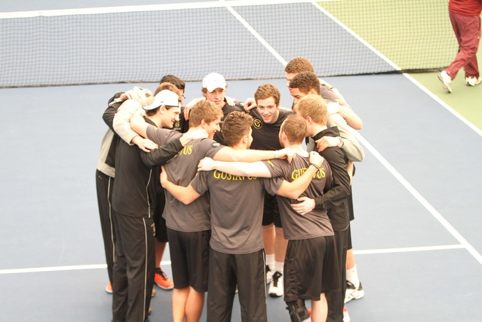 Members of the men's tennis team gather in a huddle before their matches against Hamline. The team defeated Hamline, as well as the University of Wisconsin-Eau Claire and the University of Northwestern-St. Paul on Feb. 11.