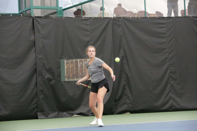 Junior Ally Baker returns a serve during a singles match against a Bethel College opponent. The team plays Minnesota State-Mankato and Southwest Minnesota State University on March 18.