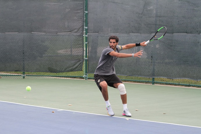 Senior Mohanad Alhouni returns a serve in a singles match Sept. 30. Alhouni defeated teammate Zach Ekstein in the tournament final to win his third consecutive regional singles title.