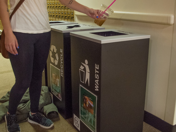 A student throws away their cup into one of the nearby waste bins.
