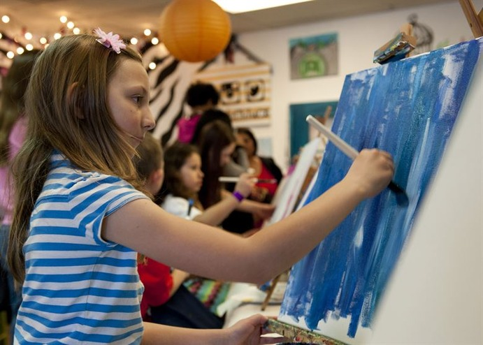 A young student expressing herself through painting.