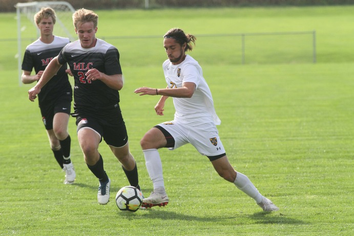 Junior Luke Laurich dribbles the ball past a Martin Luther midfielder.