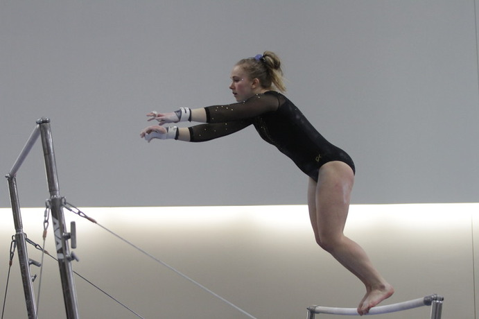 First-year Ashley Goetl competes on the uneven bars for the Gusties during a meet earlier this season. Despite finishing third of three teams the Gusties posted a score of 184.8, the highest this season.